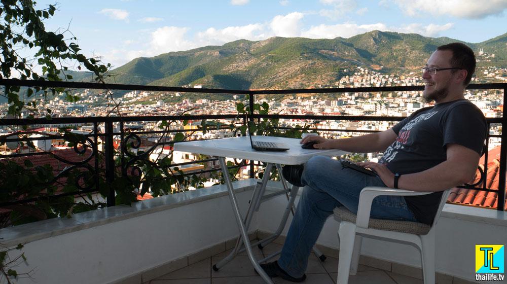 Мужчина за ноутбуком на фоне гор